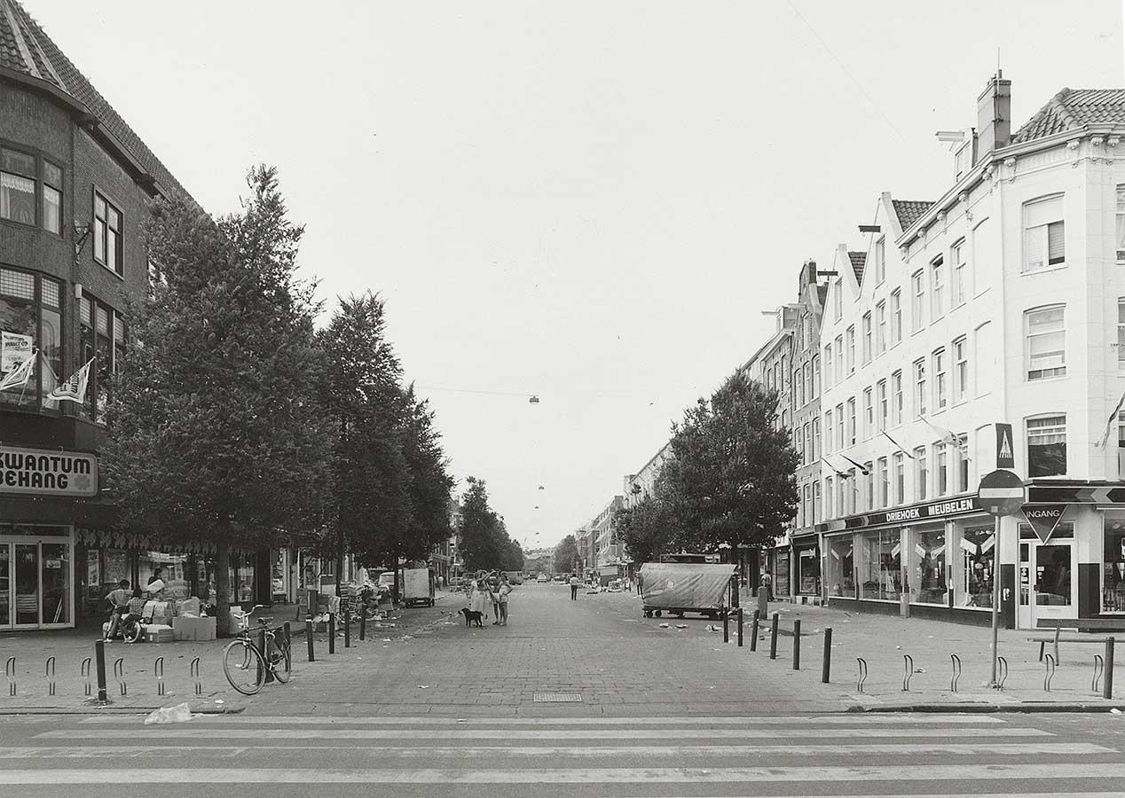 Dapperstraat gezien vanaf Eerste van Swindenstraat. Geen markt, wel nog wat troep van de markt. Groepje met hond staat in de straat.