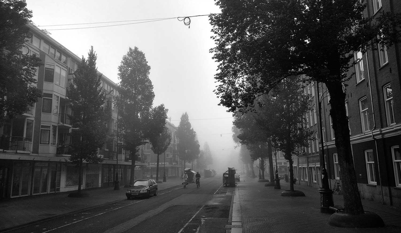 Zwart-wit foto van mistige Dapperstraat in de ochtend. Twee fietsers komen richting fotograaf. Einde straat niet te zien door dikke mist.