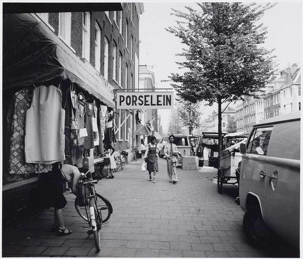 Uithangbord 'Porselein', stelletje loopt richting camera, man in pak houdt jasje in hand.