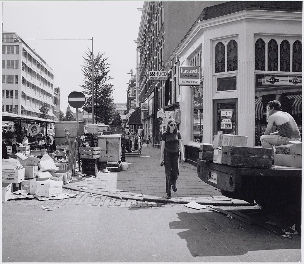 Man zittend op dozen op achterzijde vrachtwagen. Vrouw steekt over. Links stukje Dappermarkt te zien met bergje lege dozen.