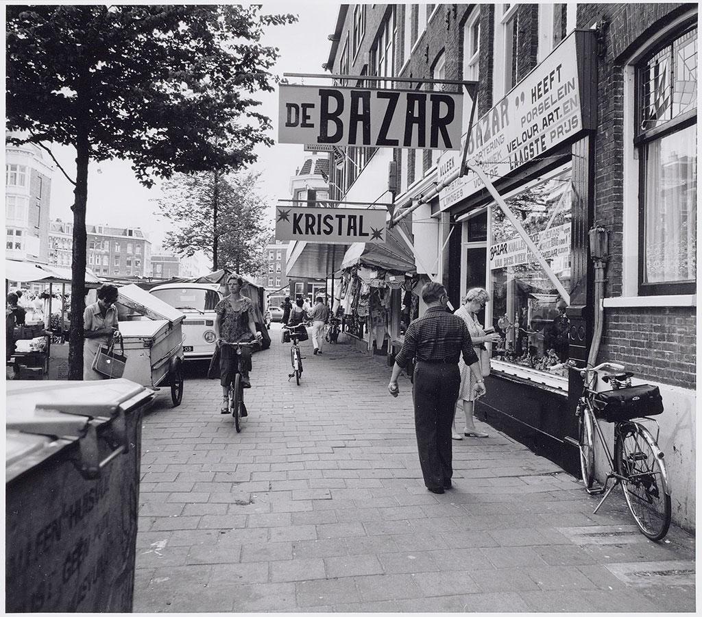 """Straat met uithangborden """"Kristal"""" en """"De Bazar"""". Voetgangers en een fietser op de stoep."""