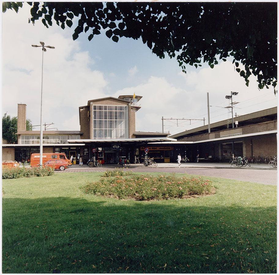 Hoofdingang Muiderpoortstation gezien vanaf grasveldje in het midden Oostspoorplein
