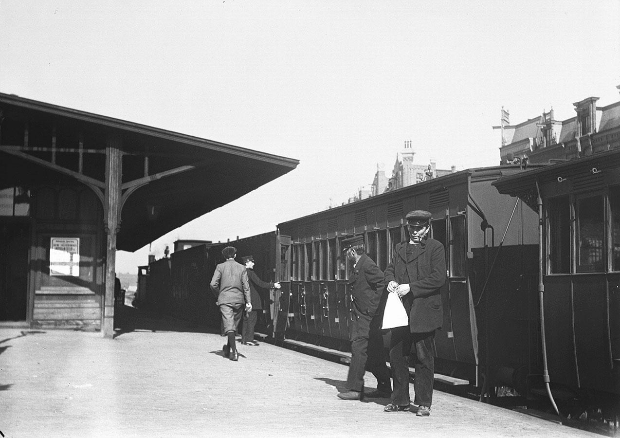 Perron van oude Muiderpoorstation met oude treinwagons en paar mensen op perron
