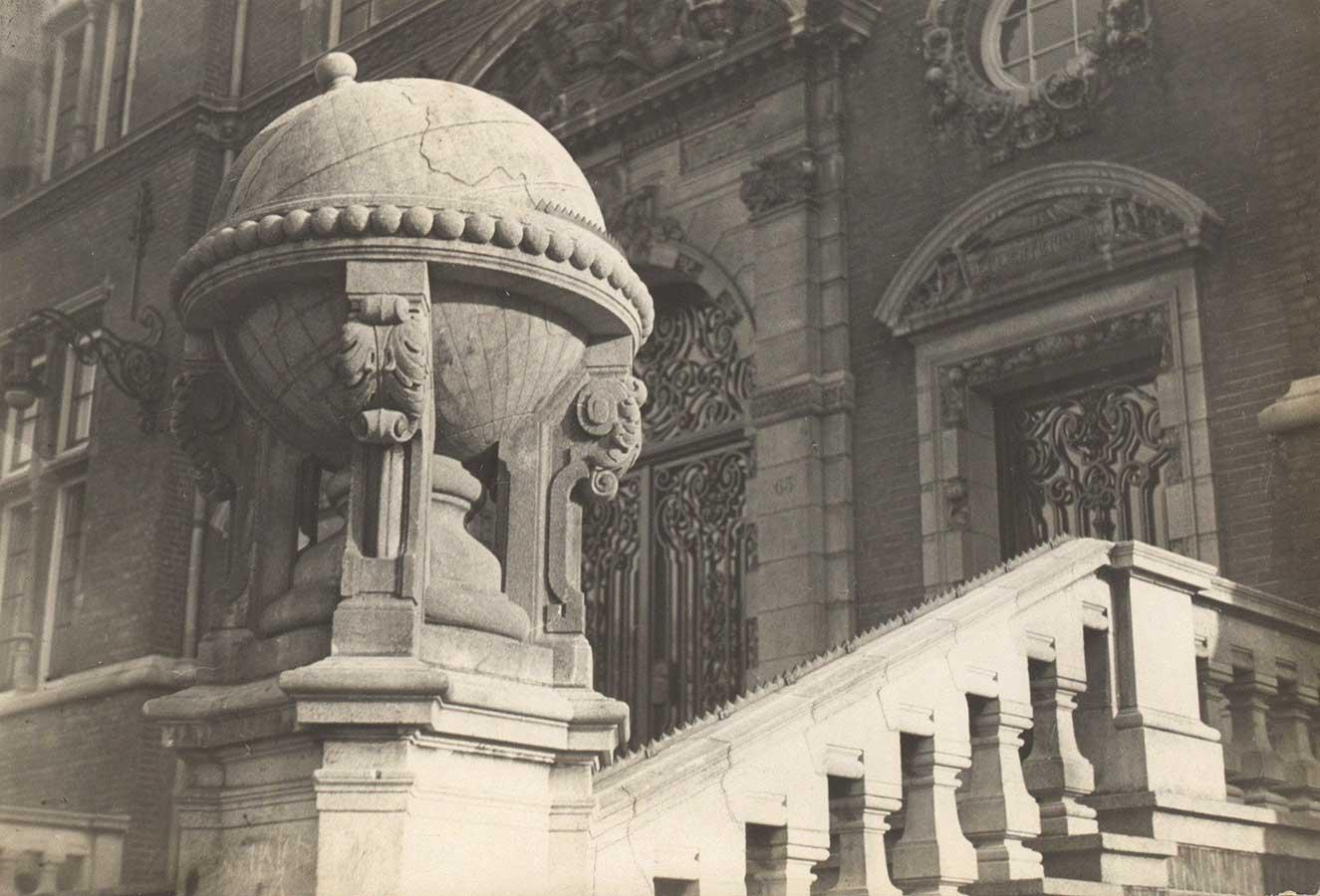 Globe van natuursteen aan de trap bij hoofdingang
