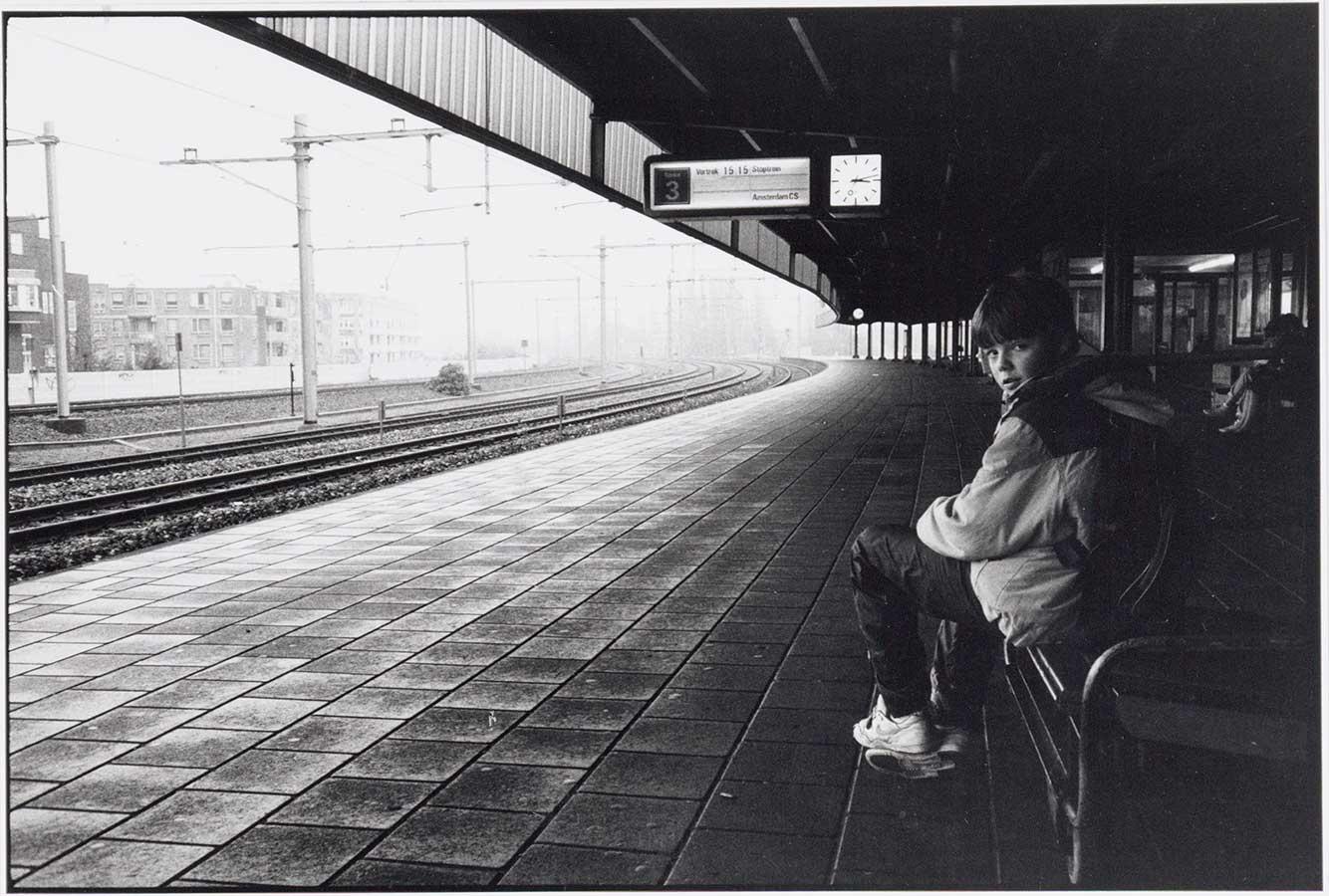 Perron 3 in 1990 met op voorgrond kind dat vanaf bankje de camera in kijkt.