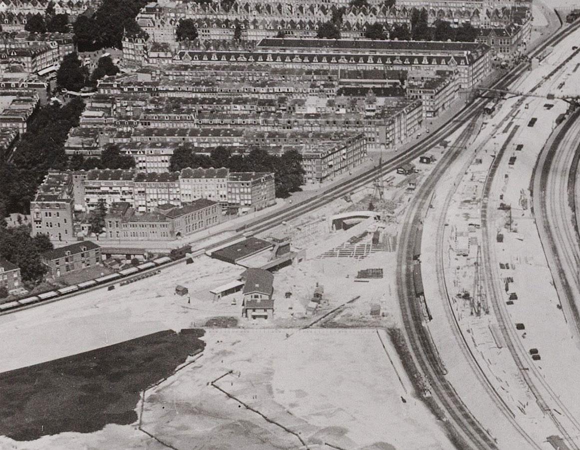 Luchtfoto van het opspuiten van het terrein voor het nieuwe Muiderpoortstation. Grote zandvlakte met station in aanbouw.