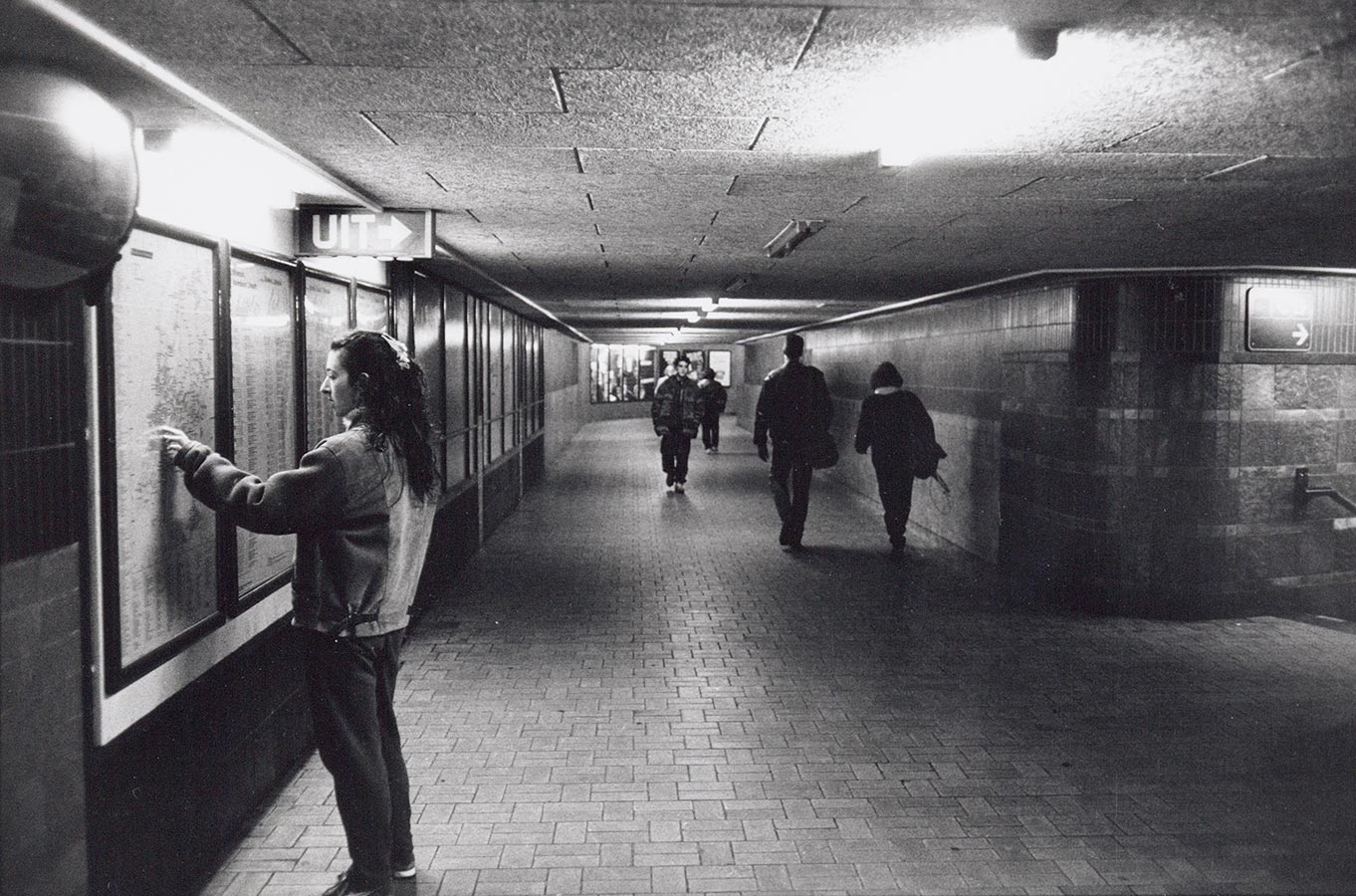 Gangen naar de sporen op Muiderpoortstation. Man bekijkt kaart met ov-informatie aan de muur.