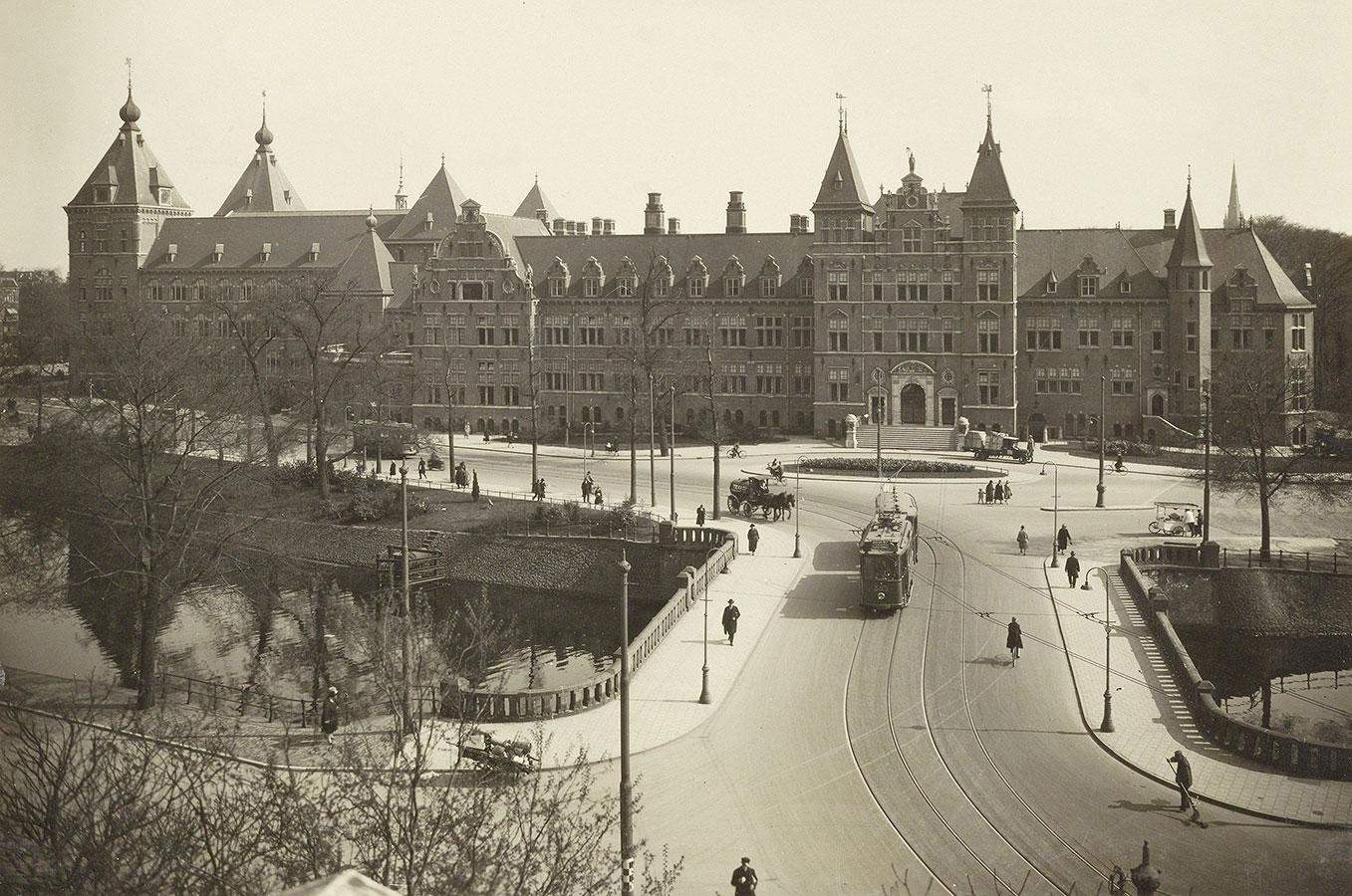 Foto vanaf Muiderpoort met zicht op brug waar tram en een paard met wagen gaat. ook voetgangers en een man die de straat veegt zijn te zien.