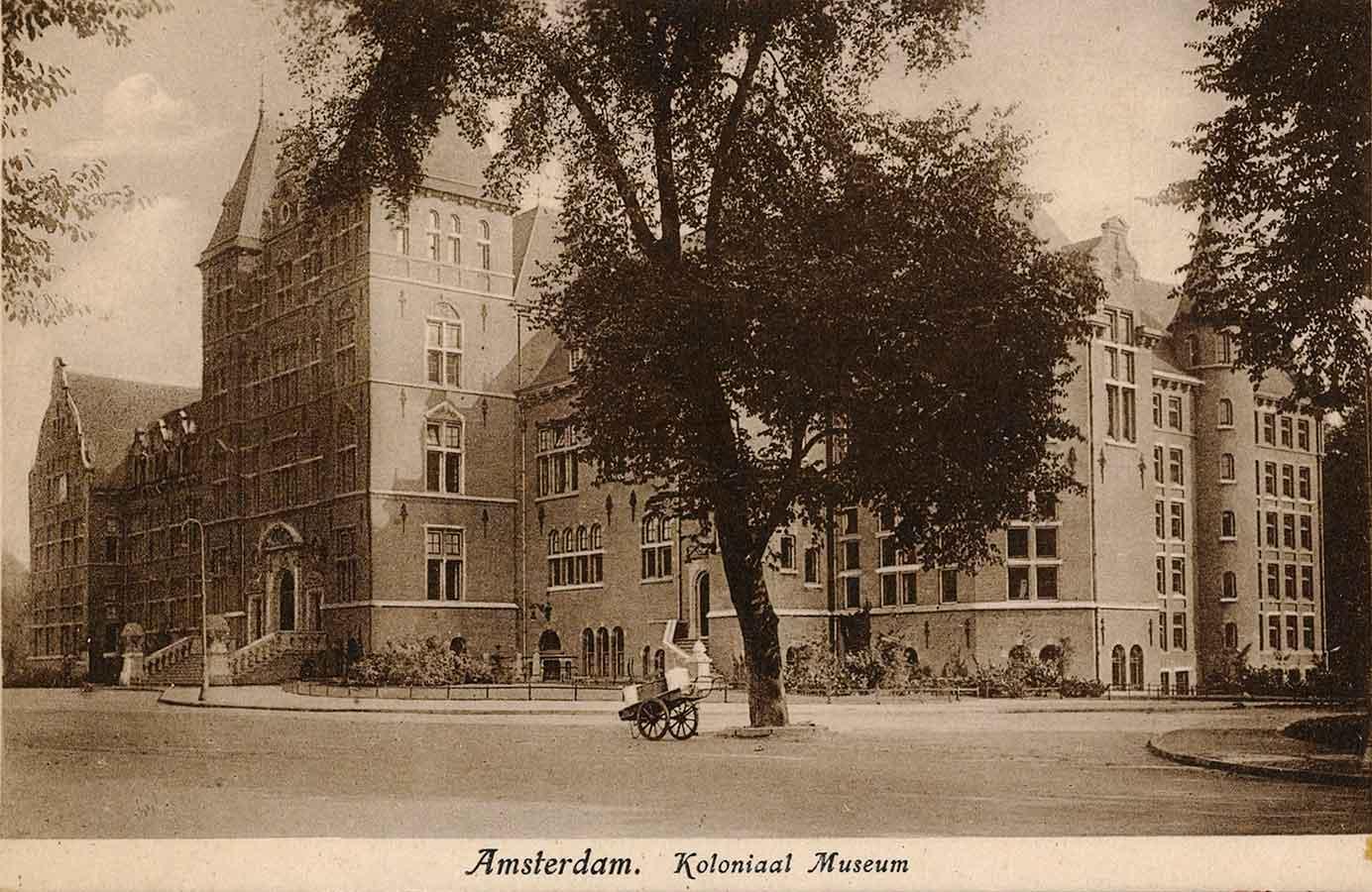 Briefkaart met tekst 'Koloniaal Museum'. Foto genoemen vanaf Mauritskade vanaf de rechterzijde richting ingang. Lege straat met geparkeerde handkar.