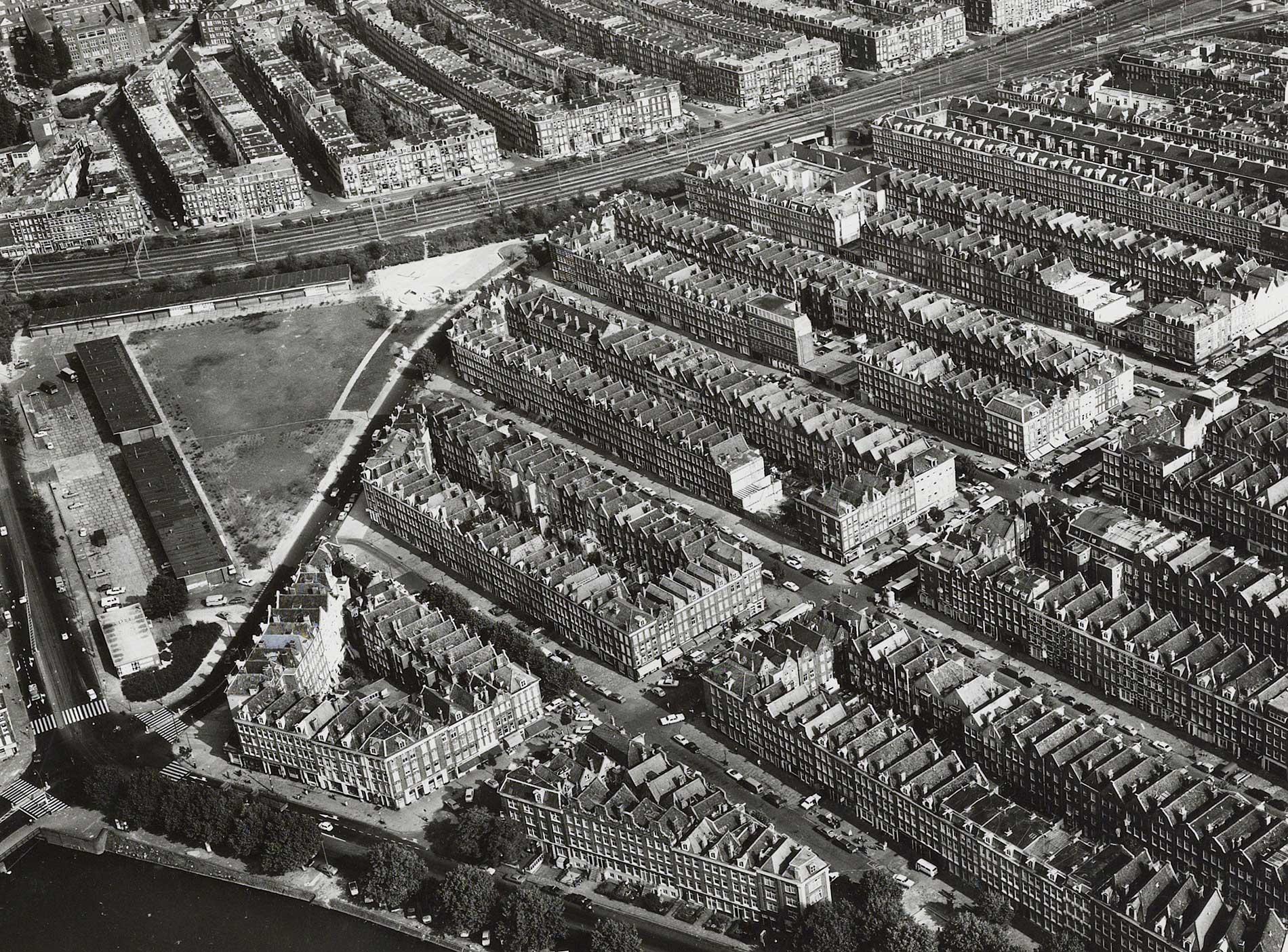Luchtfoto waarbij terrein waarbij de Roomtuintjes nog een garage met grasveld erachter is.