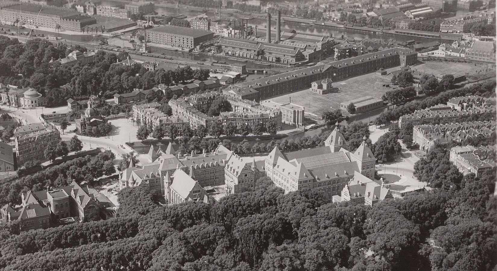Luchtfoto van KIT met op voorgrond bomendek Oosterpark. Terrein achter Alexanderkazerne nog een grasvlakte