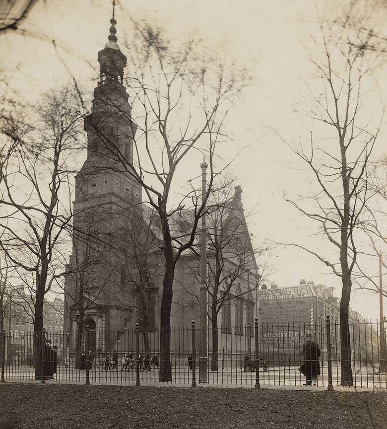 Muiderkerk gezien vanuit Oosterpark waarbij nog geen struiken voor de hekken staan. Bomen zijn kaal waardoor Linnaeusstraat goed zichtbaar is.
