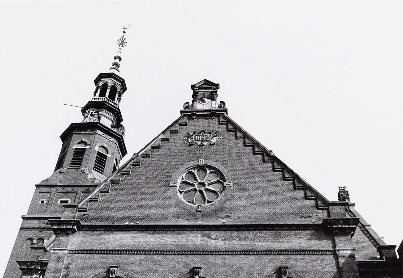 Bovenste gedeelte voorgevel Muiderkerk met toren op de achtergrond.