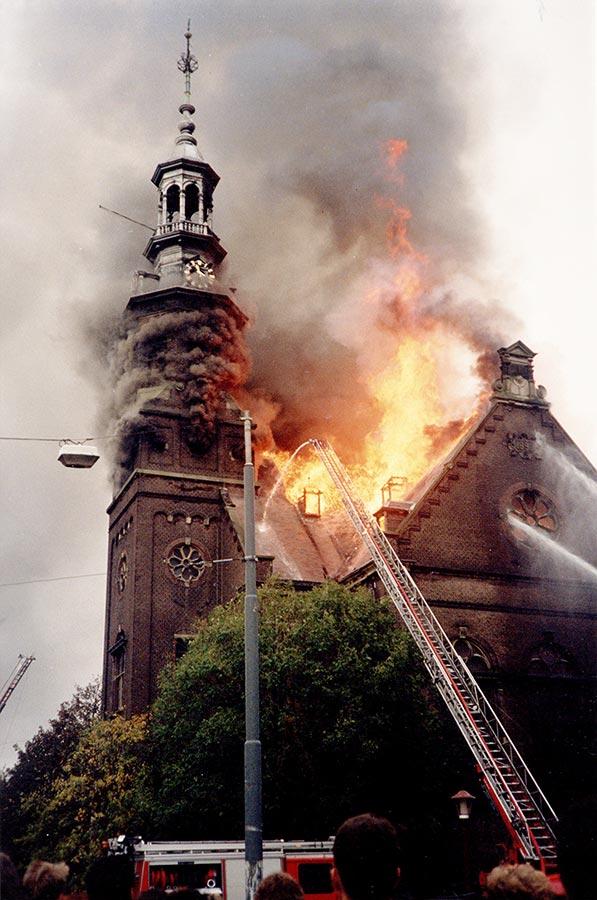 Kerk in brand, vlammen worden geblust door brandweerwagens