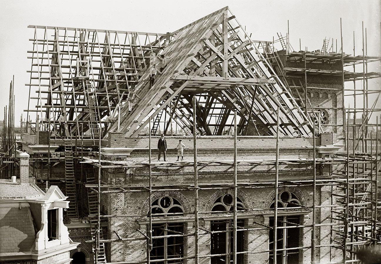 Bouw Muiderkerk gezien vanaf 1e van Swindenstraat. man (architect?) en jongen poseren op steiger. Op het houten geraamte van dak staan werklui.