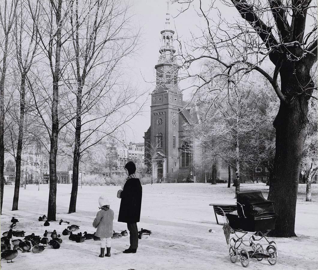 Moeder en dochtertje voeren eenden in besneeuwd Oosterpark, Muiderkerk op de achtergrond