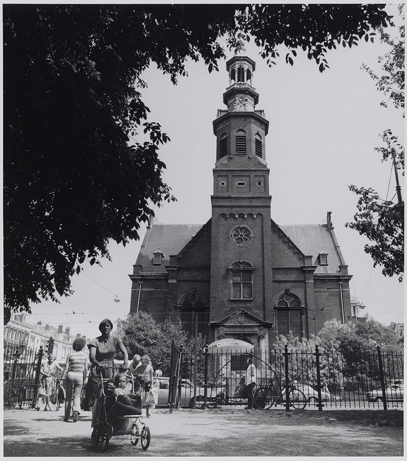 Muiderkerk gezien vanaf Oosterpark. Vrouw met kinderwagen loopt park in. Voor het park een man met ventwagen (ijsco?)