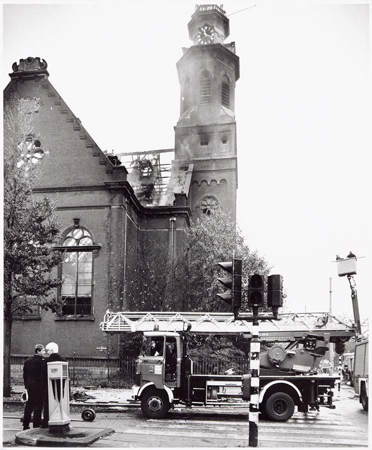 Muiderkerk met afgebrand dag. Brandweerauto staat in Eerste van Swindenstraat