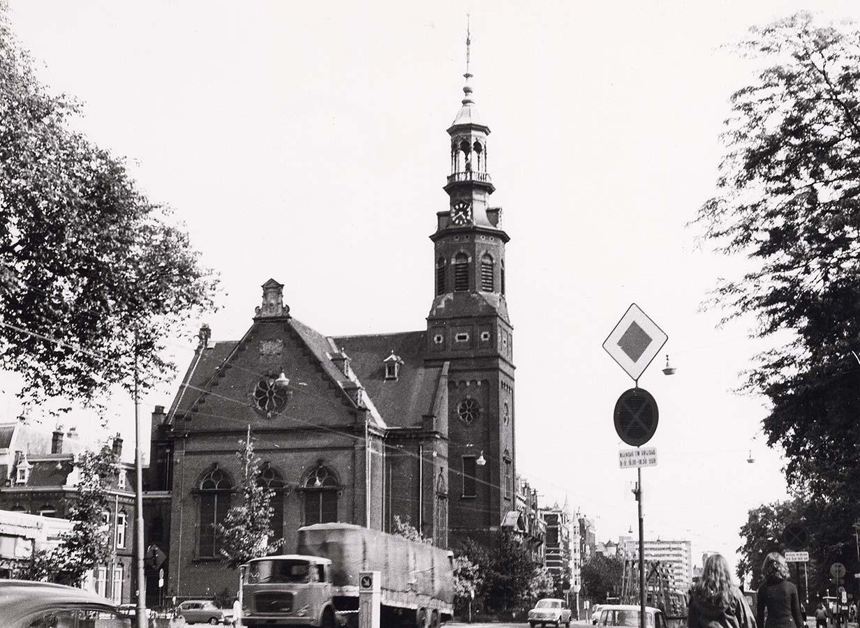 Muiderkerk gezien richting Middenweg. Rechts verkeersbord voorrangsweg.