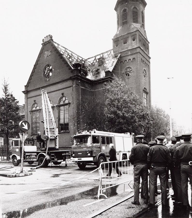 Muiderkerk na brand. Brandweerauto's en agenten staan er nog. Dak afgebrand.