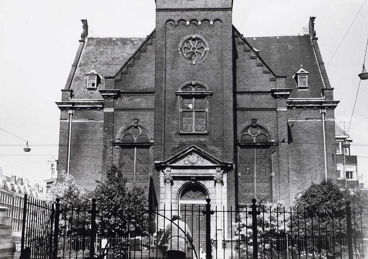 Onderste dele Muiderkerk gezien vanaf Oosterpark. Op de rug gezien een venter met wagen.