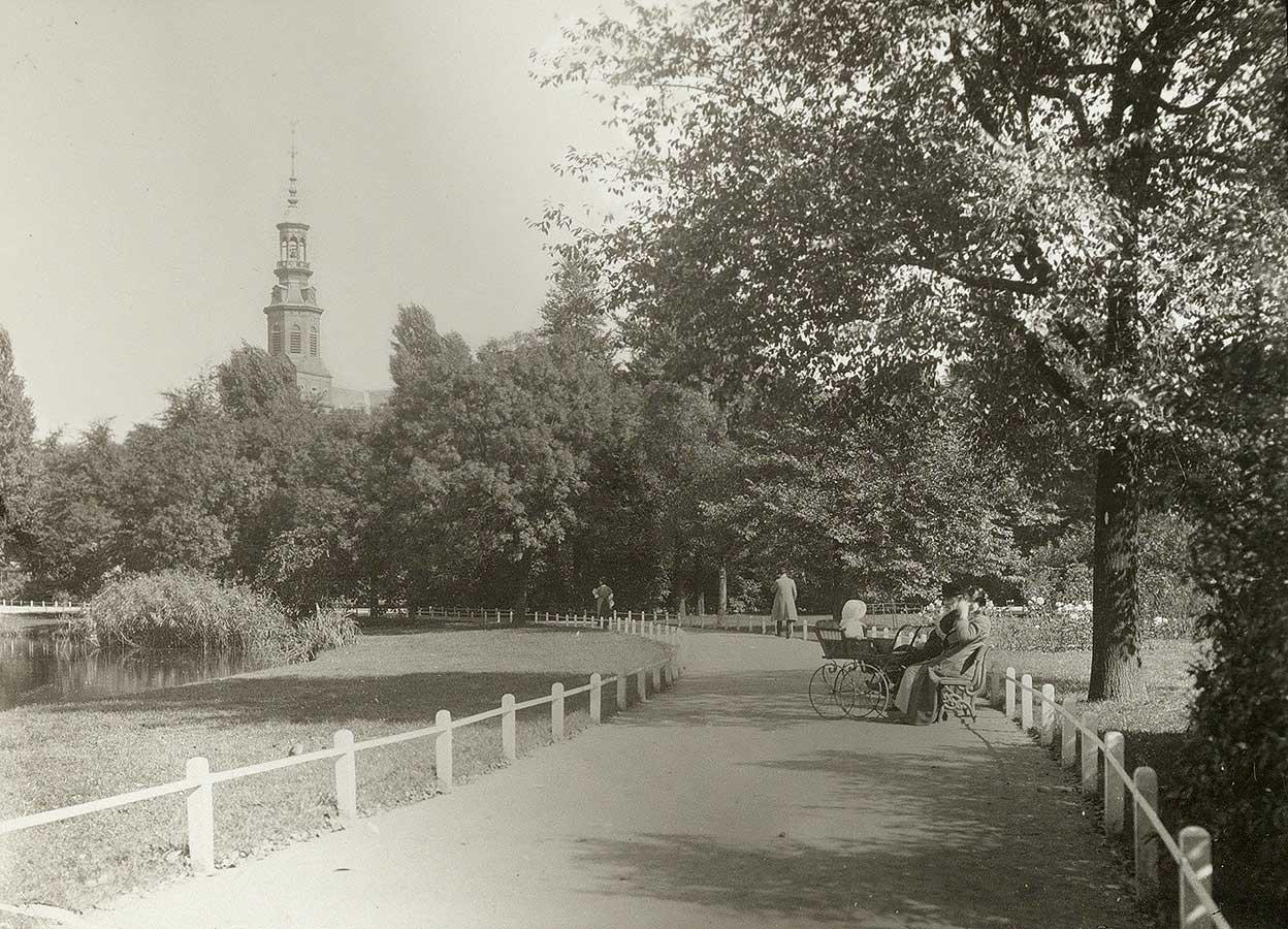 Foto op wandelpad genomen in Oosterpark. Stel op bankje met kinderwagen. Links stukje van vijver en op de achtergrond steekt toren Muiderkerk boven de bomen uit.