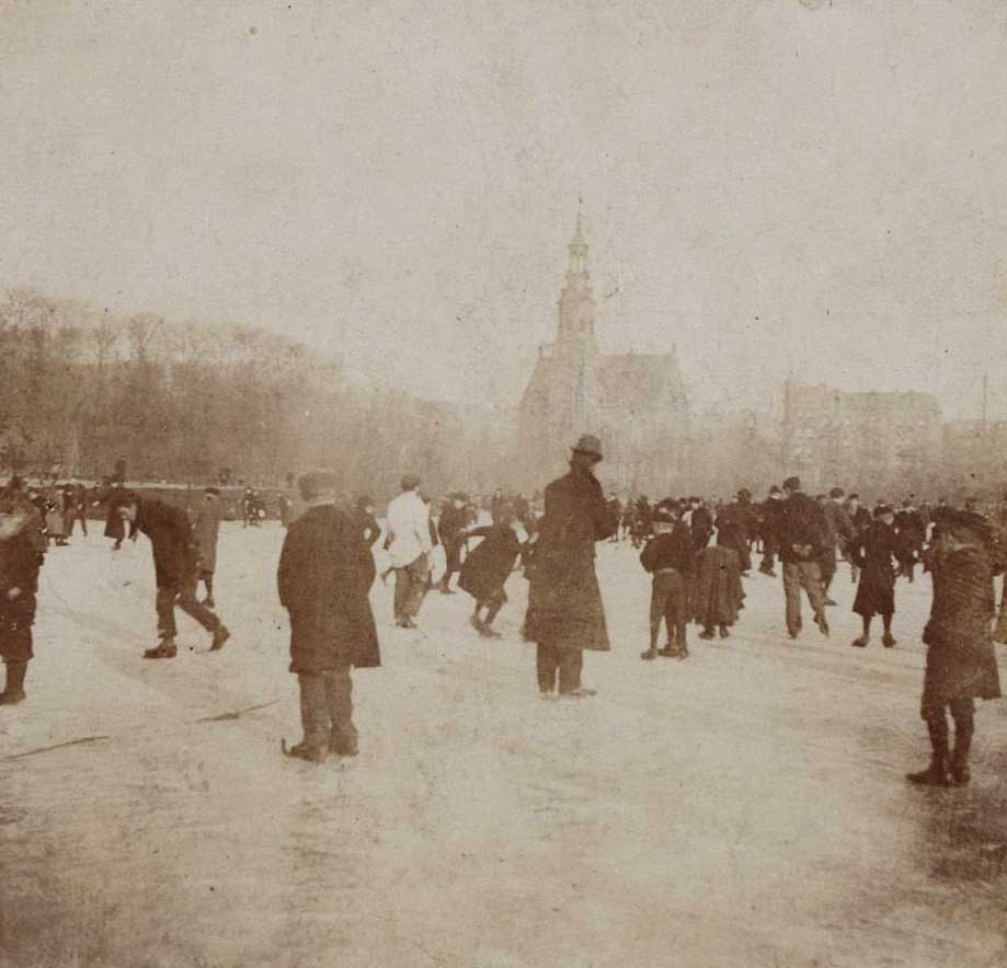 Mensen op de bevroren vijver in Oosterpark. Vaag op de achtergrond de Muiderkerk