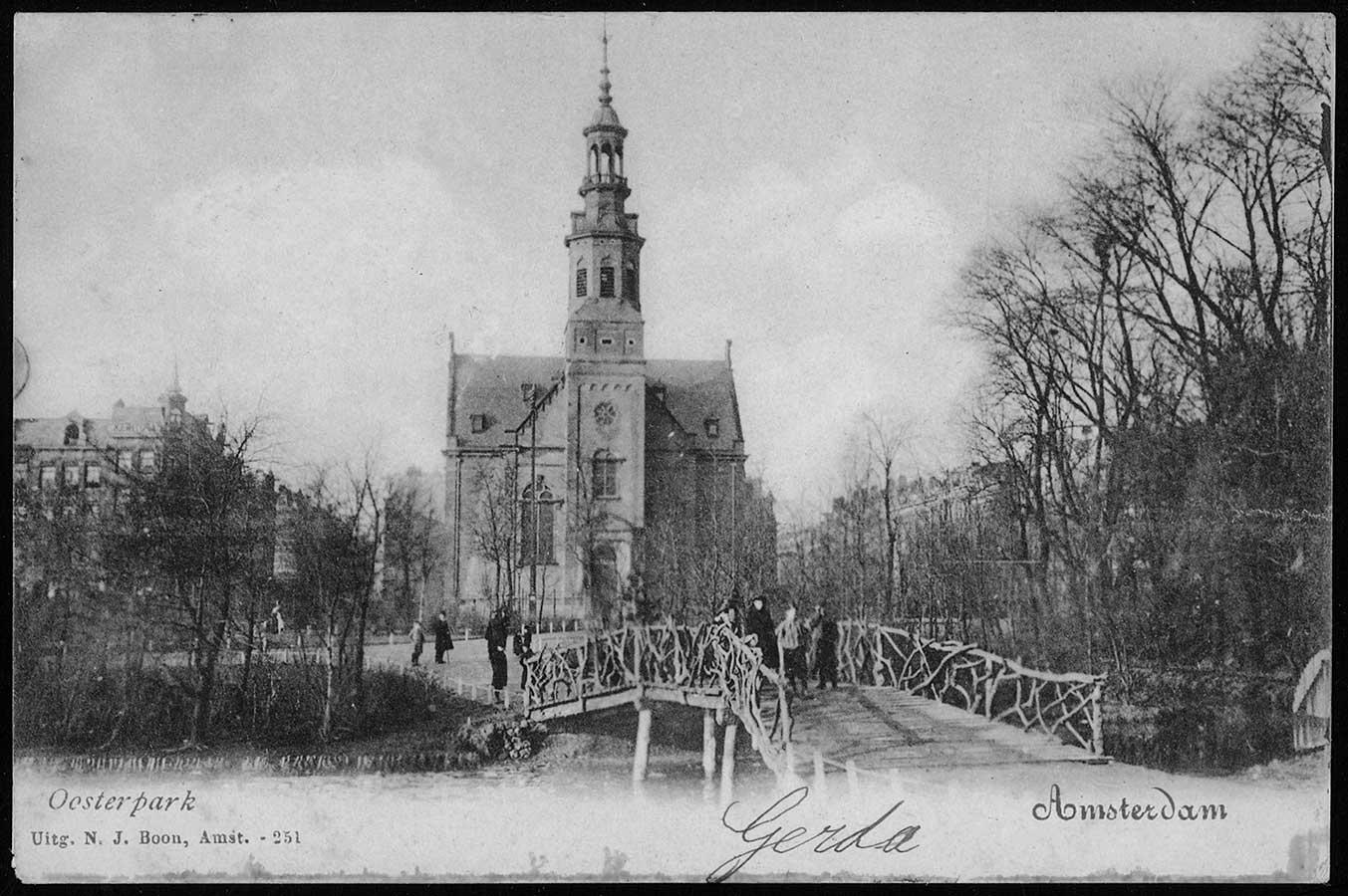 Houten bruggetje in Oosterpark met mensen die poseren, niet ver op de achtergrond de Muiderkerk