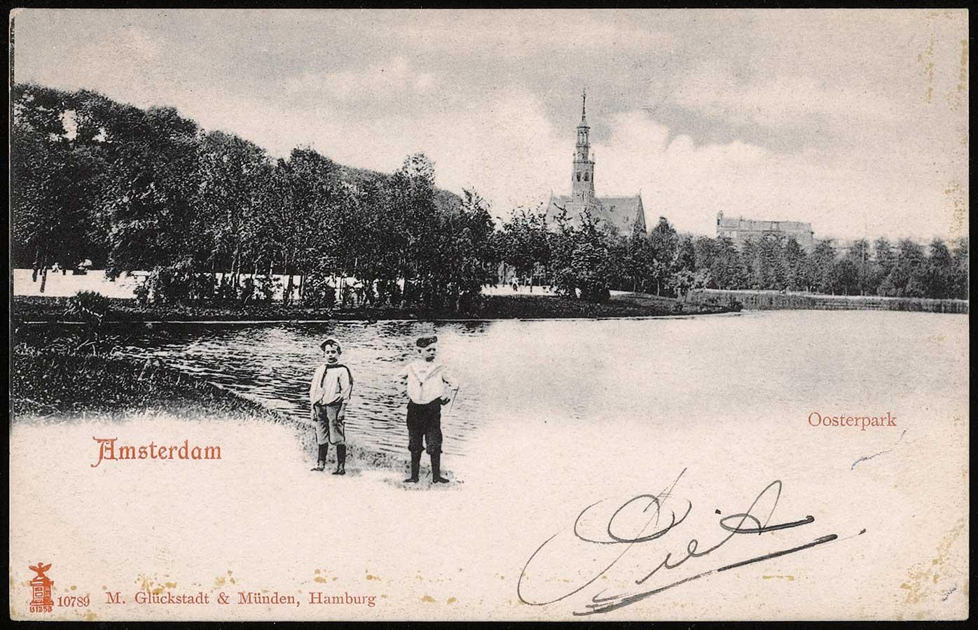 Twee kinderen in 1903 poserend bij vijver in Oosterpark met op achtergrond Muiderkerk