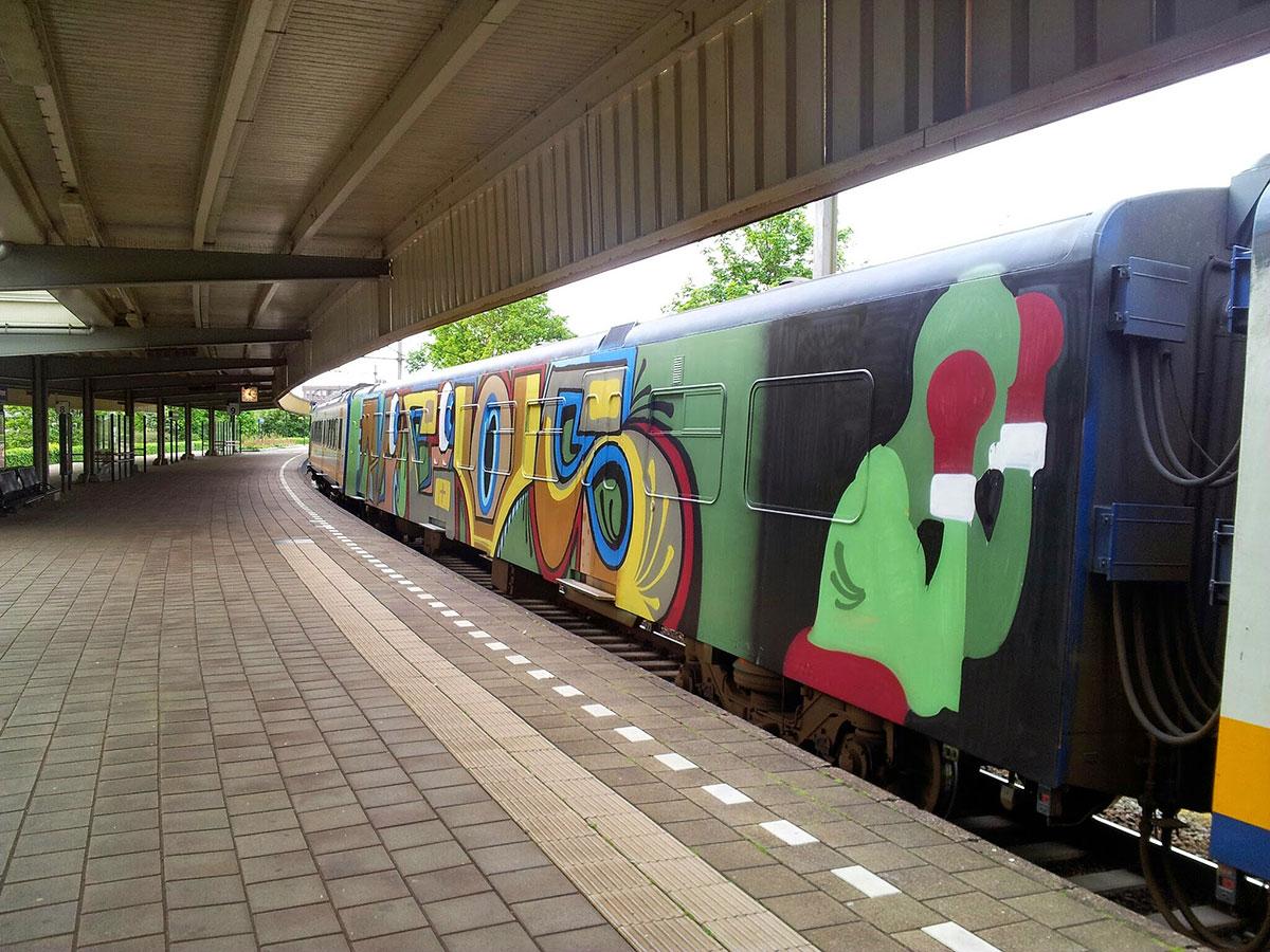 Perron 8 met treins waarbij een treinstel een complete graffiti-piece is