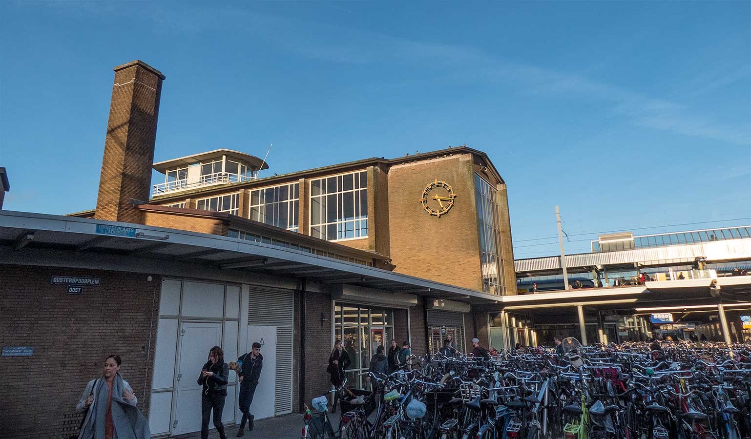 Oostspoorplein met rechts fietsenstalling en links stationsgebouw en zicht op klok