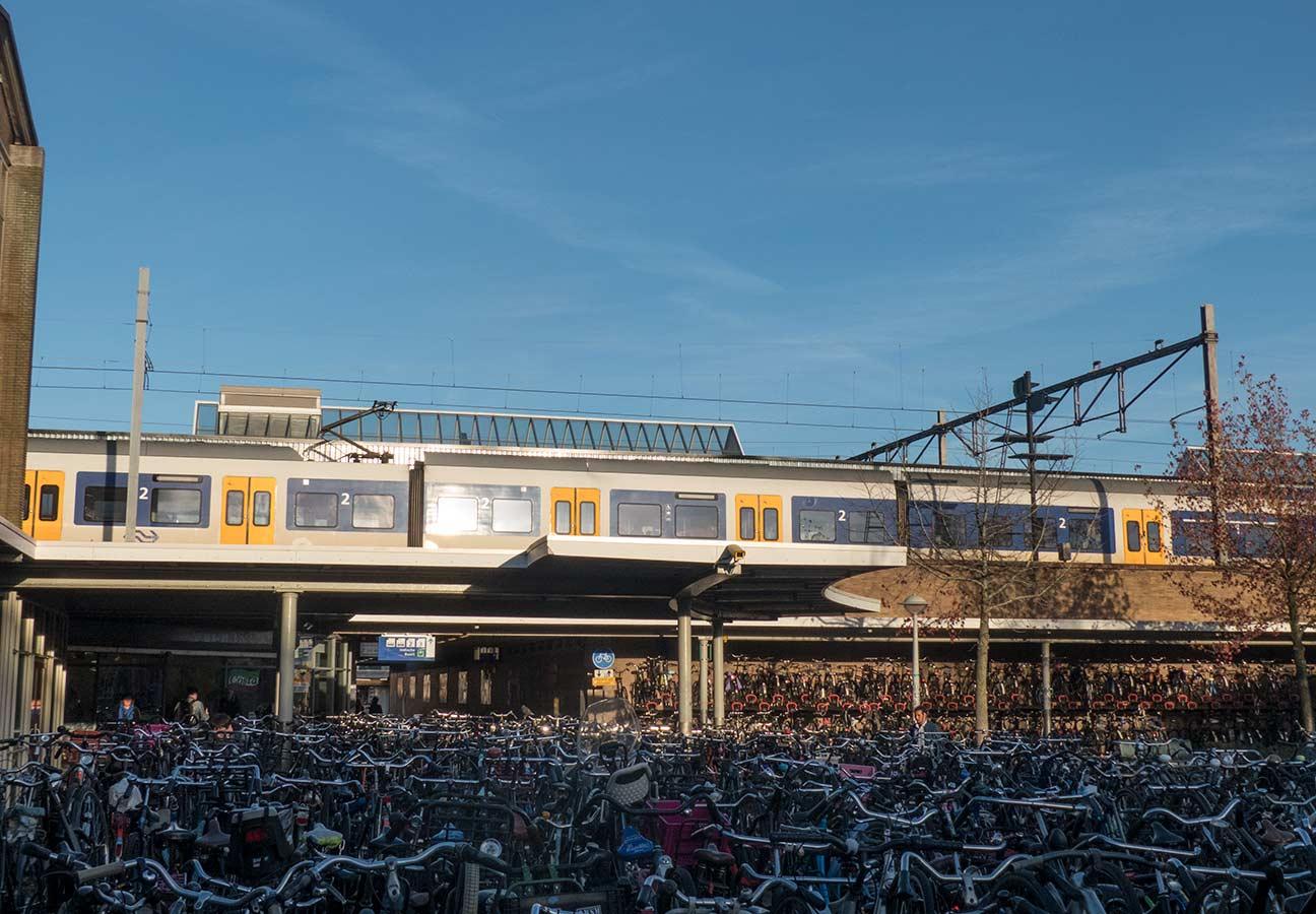 Oostspoorplein met zicht op perron 4 waar een trein staat. Op voorgrond volle fietsenstallig