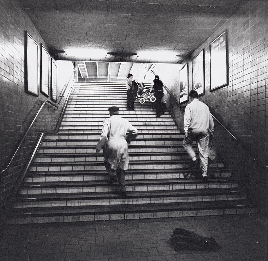 Trap maar perron. Twee mensen tillen kinderwagen de trap op.