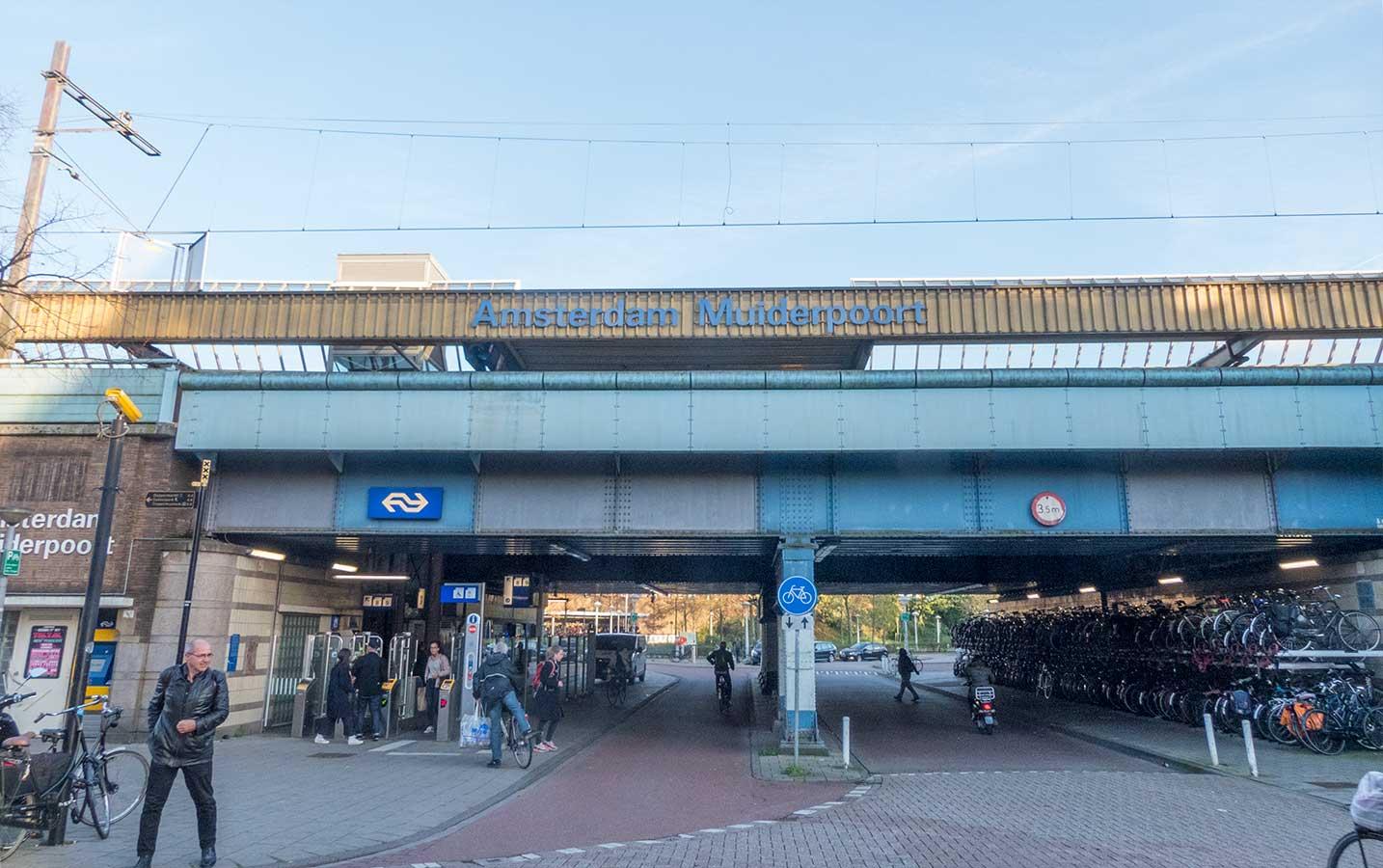 Ingang Muiderpoortstation aan einde Domselaerstraat. Viaduct met fietsenstalling eronder