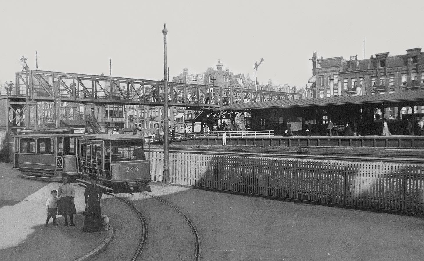 Oude station Muiderpoort gezien vanuit Pontanusstraat. Op voorgrond twee kinderen en vrouw met hondje. Daarachter tram 244