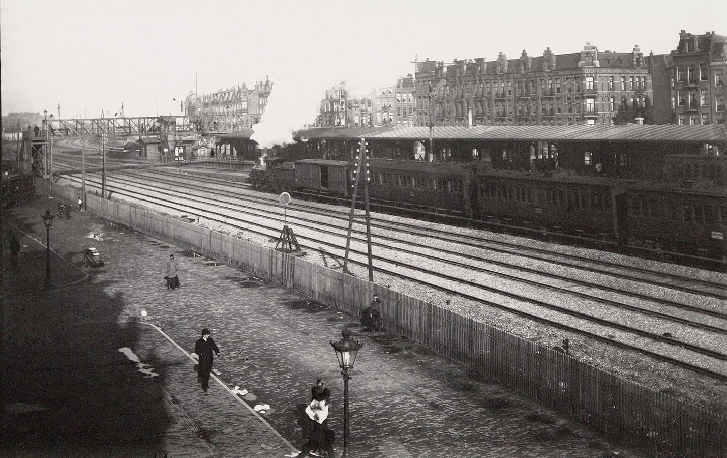 Oude Muiderpoortstation gezien richting Celebesstraat. Trein voor het perron, veel stoom uit locomotief