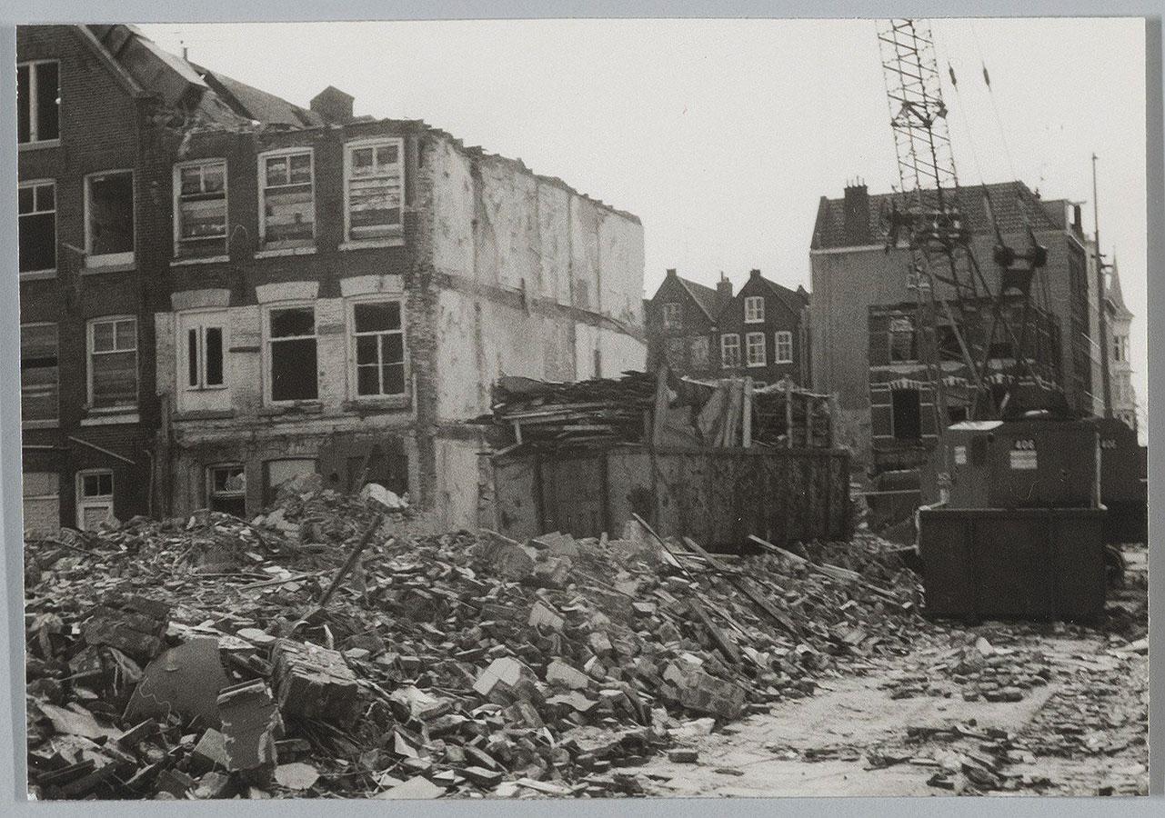 Kraanwagen rechts. Veel puin op de voorgrond, container met troep naast half afgebroken pand.