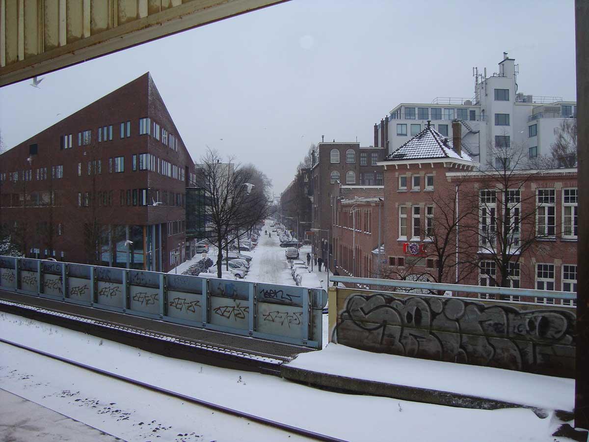 Zicht op besneeuwde Domselaerstraat vanaf perron Muiderpoortstation