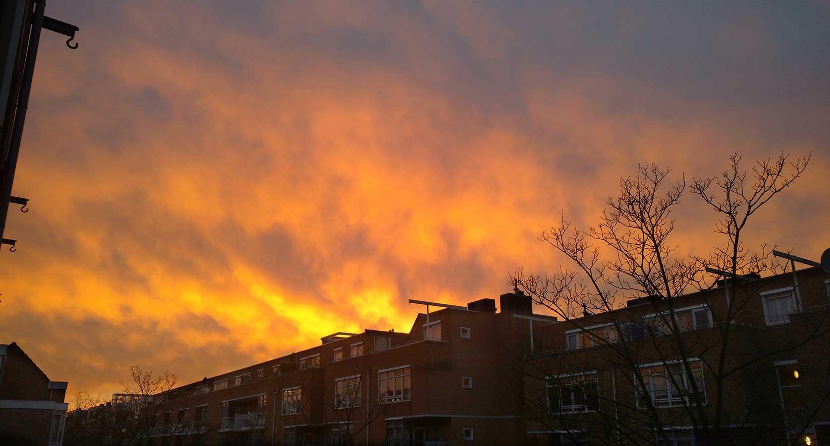 Vanaf 2de verdieping foto van oranje-gele lucht boven Commelinstraat