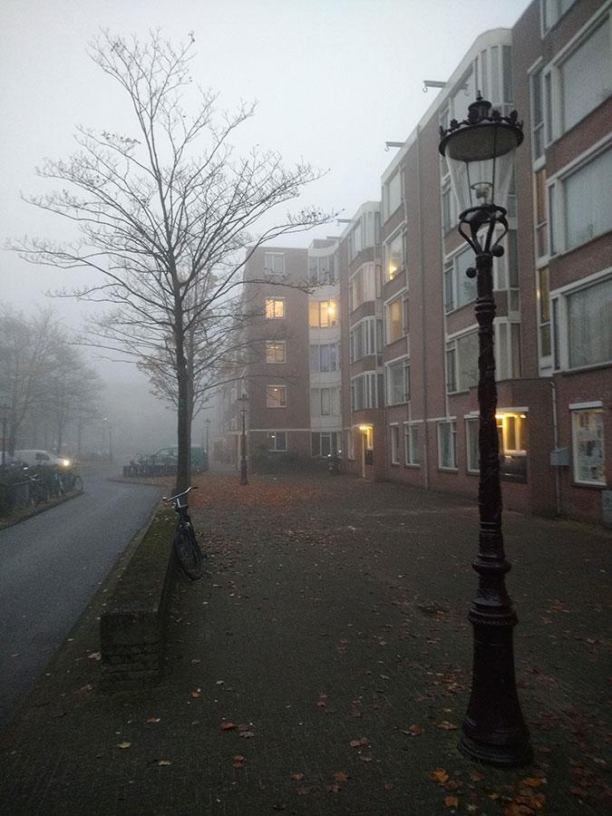 Einde Commelinstraat in de mist, hier en daar brandt licht in appartementen.