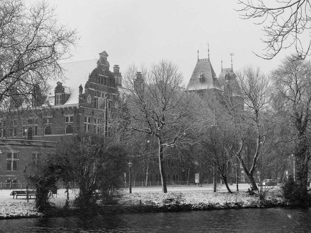 Besneeuwd KIT gezien vanaf Alexanderkade, rechts de torens van de ingang aan Mauritskade