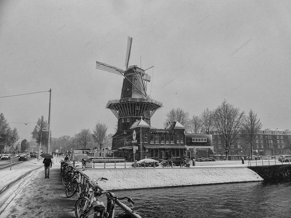 Zwart-wit foto vanaf brug richting molen de Gooyer tijdens een sneeuwbui